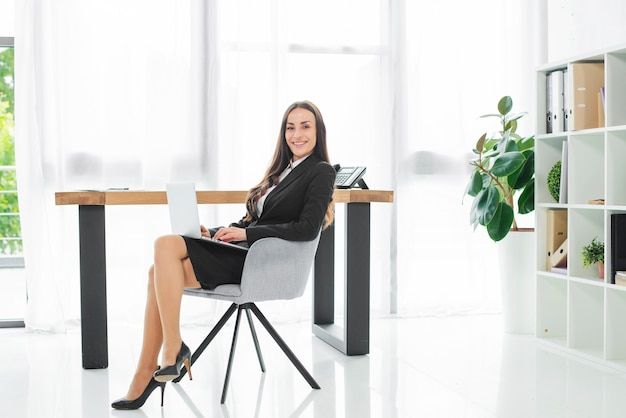 Souriante jeune femme d'affaires assis sur le lieu de travail avec un ordinateur portable sur ses genoux Photo gratuit