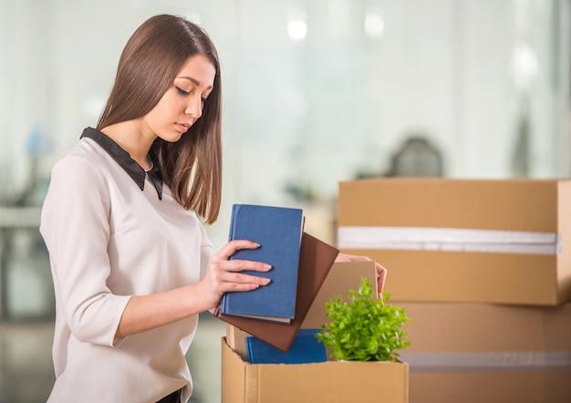 Souriante jeune femme d'affaires, emballage de boîtes au bureau. Photo Premium