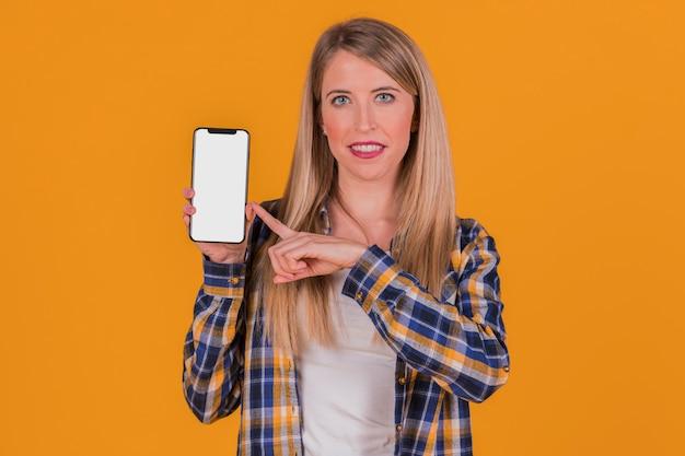 Souriante jeune femme d'affaires pointant son doigt sur un téléphone portable sur un fond orange Photo gratuit