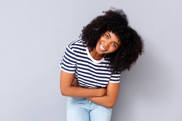 Souriante jeune femme afro-américaine sur fond gris avec les bras croisés Photo Premium