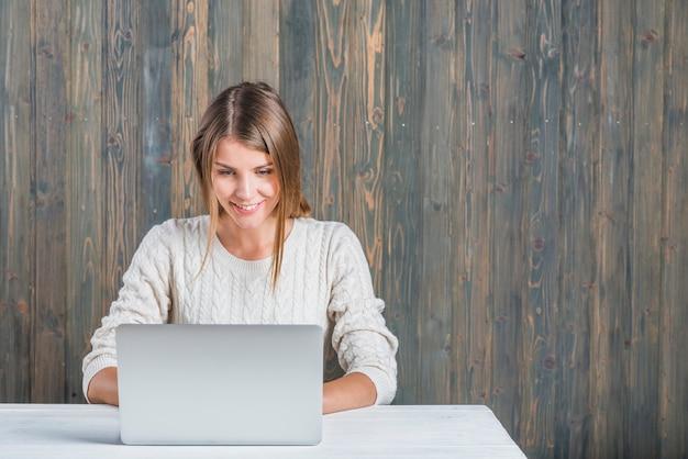 Souriante jeune femme à l'aide d'un ordinateur portable contre un mur en bois Photo gratuit