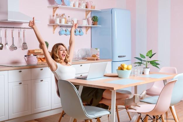 Souriante jeune femme à l'aide d'un ordinateur portable dans la cuisine à la maison. femme blonde travaille sur ordinateur, pigiste ou blogueur travaillant à la maison Photo Premium