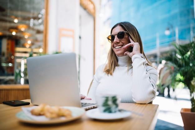 Souriante jeune femme à l'aide d'un ordinateur portable à table avec boisson et croissants au café de rue Photo gratuit