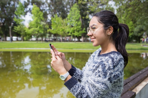 Souriante jeune femme à l'aide de smartphone dans le parc Photo gratuit