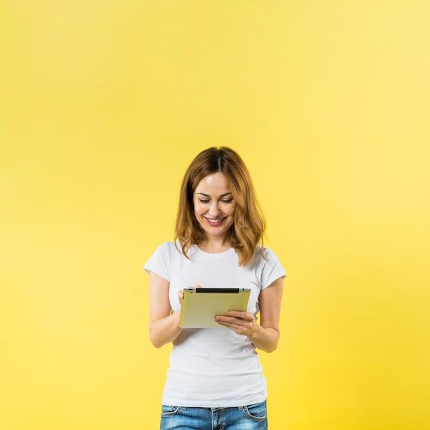 Souriante jeune femme à l'aide de tablette numérique sur fond jaune Photo gratuit