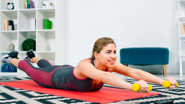 Souriante jeune femme allongée sur un tapis d'exercice rouge avec haltères jaunes Photo gratuit