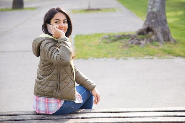 Souriante jeune femme appeler sur le téléphone et faire demi-tour dans le parc Photo gratuit