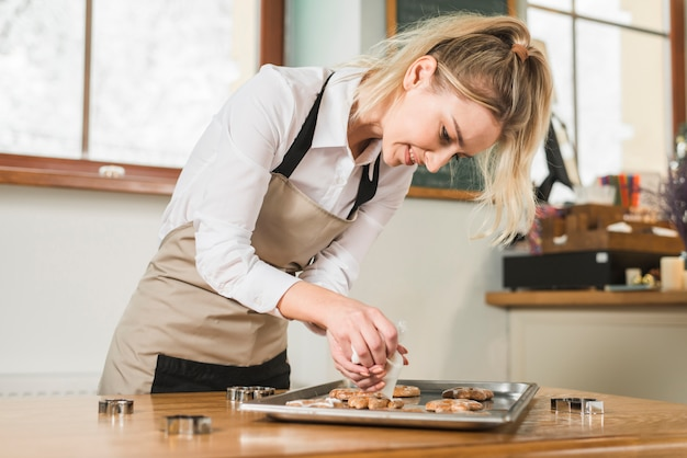 Souriante jeune femme, appliquer la crème sur les biscuits cuits au four sur la plaque de cuisson Photo gratuit