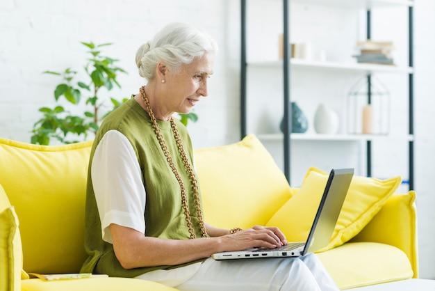 Souriante jeune femme assise sur un canapé jaune à l'aide d'un ordinateur portable Photo gratuit