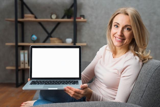Souriante jeune femme assise sur un canapé montrant son ordinateur portable Photo gratuit