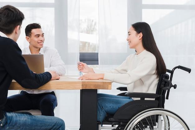 Souriante jeune femme assise sur un fauteuil roulant ayant une réunion de travail avec ses deux collègues Photo gratuit