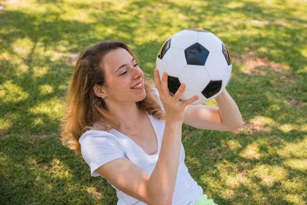Souriante jeune femme assise sur l'herbe avec le football Photo gratuit