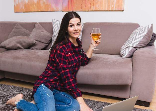 Souriante Jeune Femme Assise Près Du Canapé Tenant Un Verre En Verre à Vin Photo gratuit