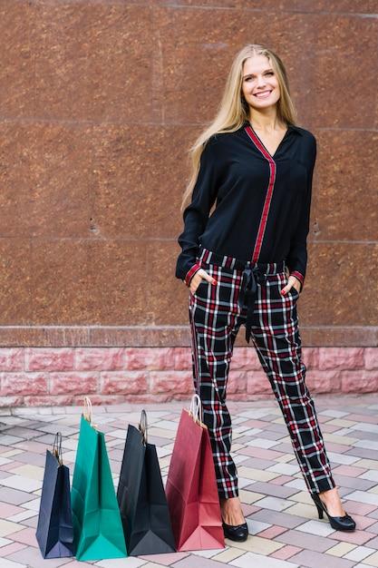 Souriante jeune femme blonde avec ses mains dans les poches, debout près des sacs colorés Photo gratuit