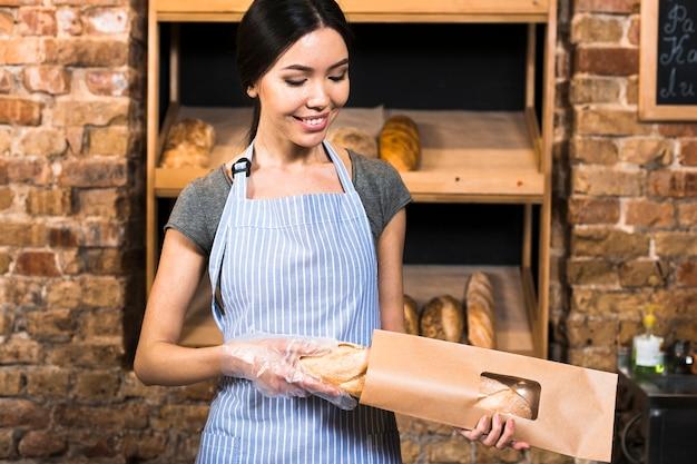 Souriante jeune femme boulangère emballant le pain baguette dans le sac en papier brun du magasin Photo gratuit