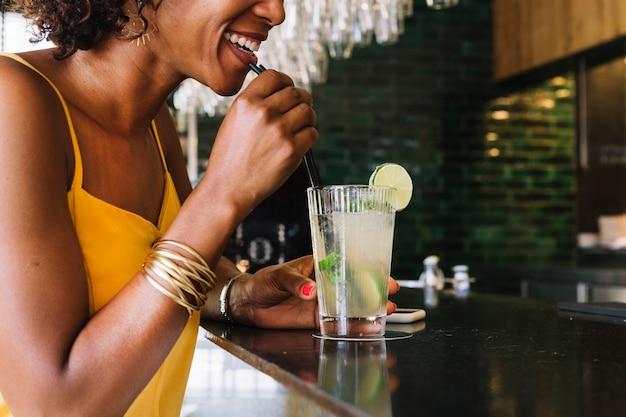 Souriante jeune femme buvant du mojito au bar du restaurant Photo gratuit