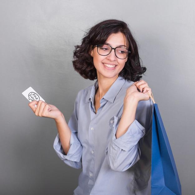 Souriante jeune femme avec carte et sac à provisions Photo gratuit