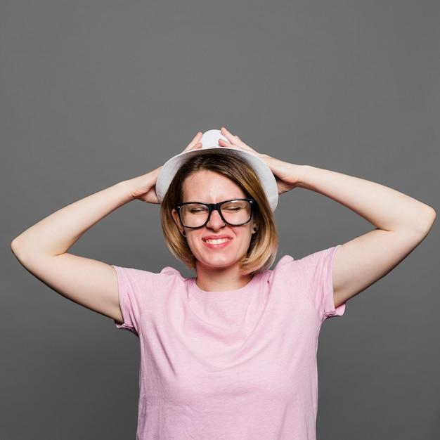 Souriante jeune femme avec un chapeau blanc sur la tête en levant le mur gris Photo gratuit