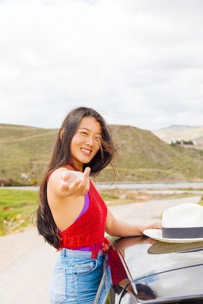 Souriante jeune femme chinoise offrant de la suivre dans la nature Photo gratuit