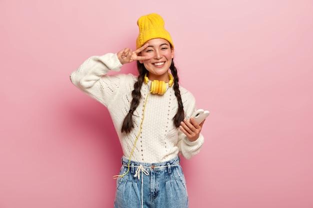 Souriante Jeune Femme Coréenne Fait Un Geste De Paix Sur Les Yeux, Tient Un Téléphone Portable Moderne, A Deux Tresses, Sourit Doucement, Porte Un Chapeau Jaune Et Un Jean, Pose Sur Fond Rose. Photo gratuit
