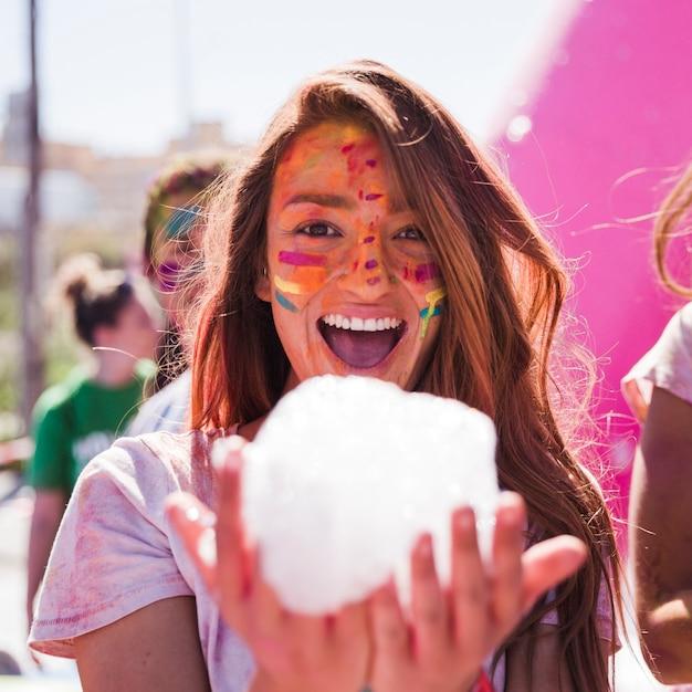 Souriante jeune femme avec la couleur holi sur son visage, tenant la mousse à la main en regardant la caméra Photo gratuit