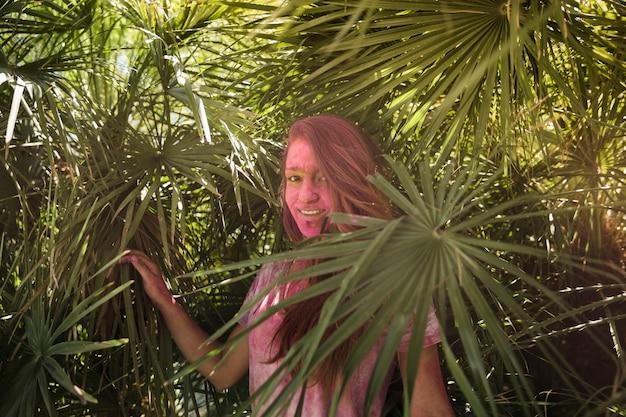 Souriante jeune femme avec la couverture de son visage en couleur holi debout près des feuilles de palmier Photo gratuit