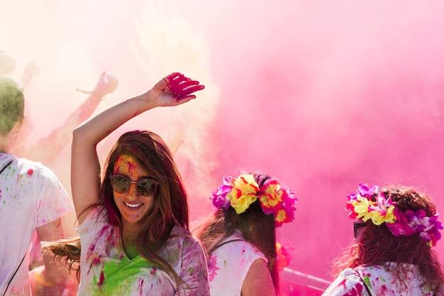 Souriante jeune femme dansant dans la couleur holi Photo gratuit
