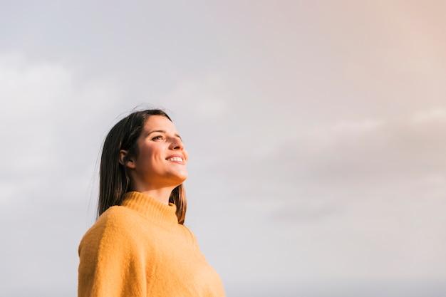 Souriante jeune femme debout contre le ciel à la recherche de suite Photo gratuit
