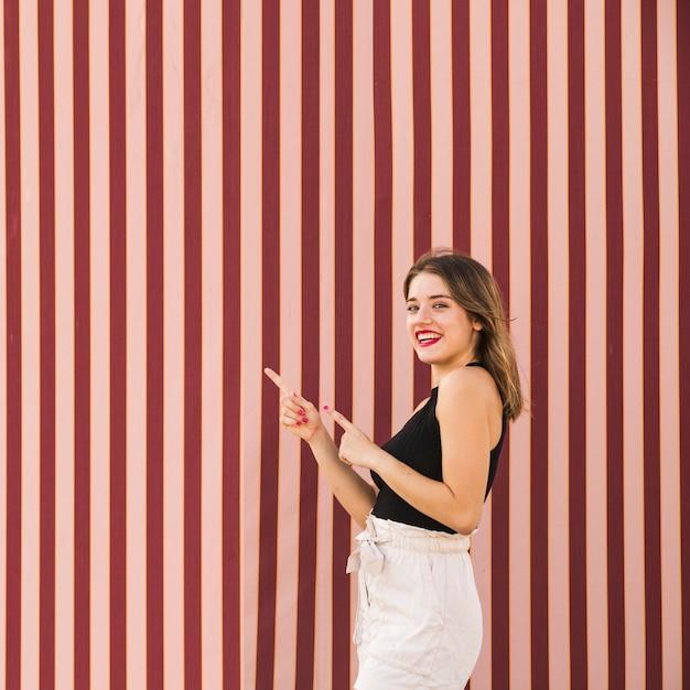 Souriante jeune femme debout devant un fond rayé, pointant les doigts Photo gratuit