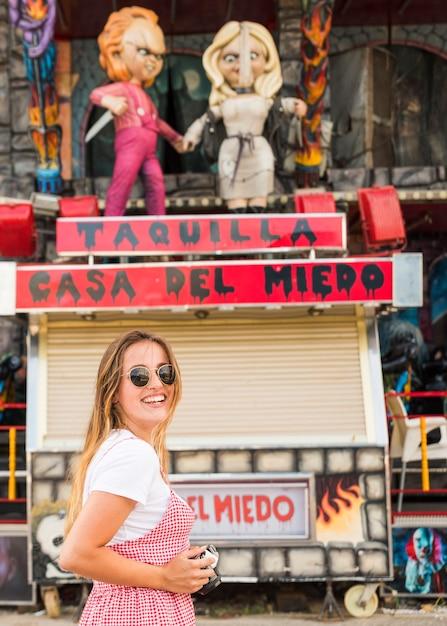 Souriante jeune femme debout devant la maison hantée Photo gratuit