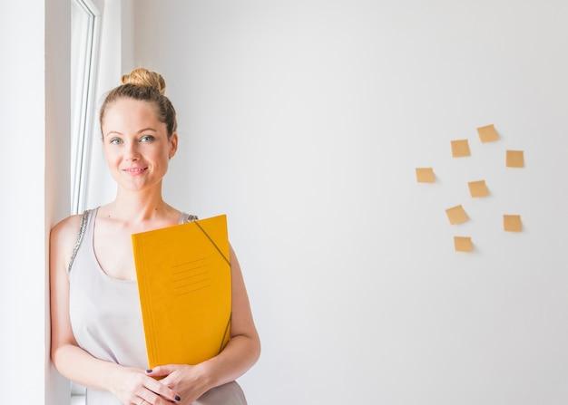 Souriante jeune femme debout devant un mur tenant des dossiers jaunes Photo gratuit