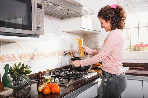 Souriante jeune femme debout près du gaz préparant des spaghettis dans la cuisine Photo gratuit