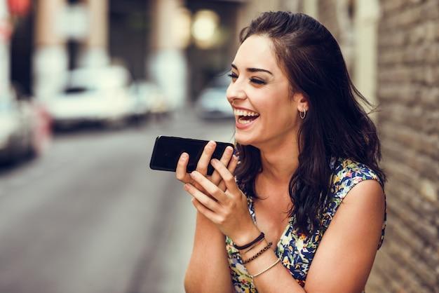 Souriante jeune femme enregistrant une note vocale dans son téléphone intelligent Photo Premium