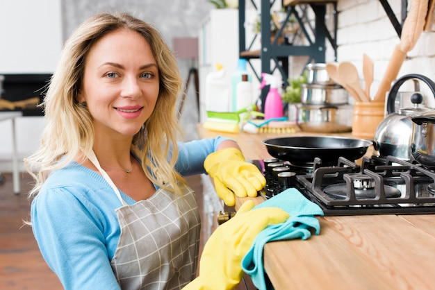 Souriante jeune femme essuyant le plan de travail de la cuisine en bois Photo gratuit