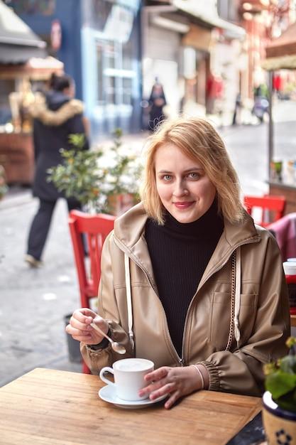 Souriante Jeune Femme Européenne Boit Du Café Au Café De La Rue Dans Le Quartier Juif Du Quartier De Fatih, Istanbul. Photo Premium