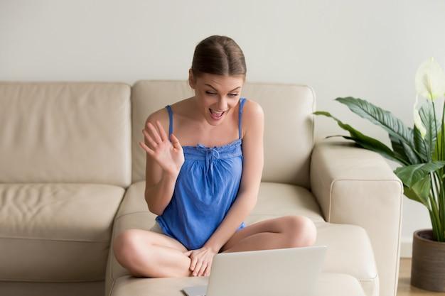 Souriante jeune femme faisant un appel vidéo à distance sur un ordinateur portable Photo gratuit