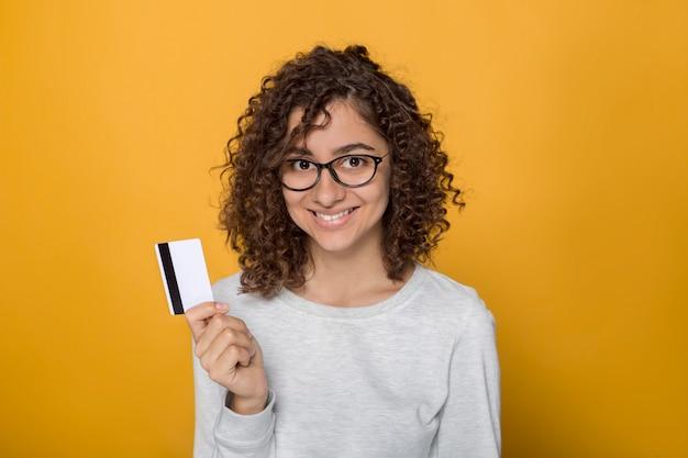 Souriante jeune femme avec des lunettes de race mixte est titulaire d'une carte de crédit. heureuse femme afro noire en studio sur fond jaune. Photo Premium