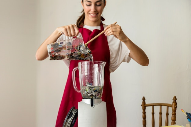 Souriante jeune femme mettant des papiers déchirés dans un mélangeur Photo gratuit