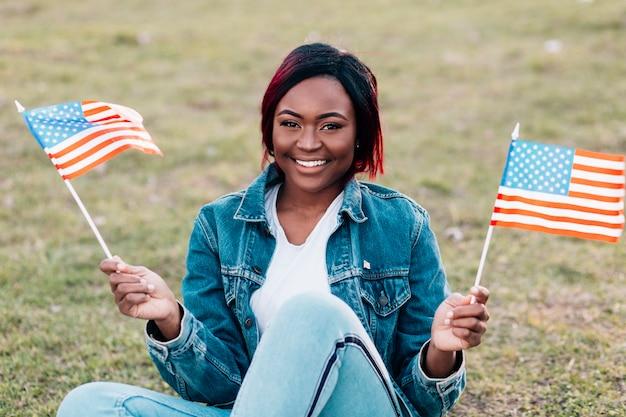 Souriante jeune femme noire avec des drapeaux américains Photo gratuit