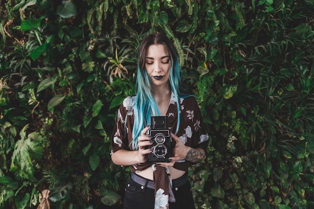 Souriante jeune femme photographiant avec appareil photo vintage Photo gratuit