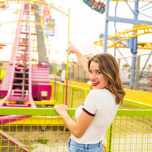 Souriante jeune femme pointant le doigt sur les montagnes russes Photo gratuit