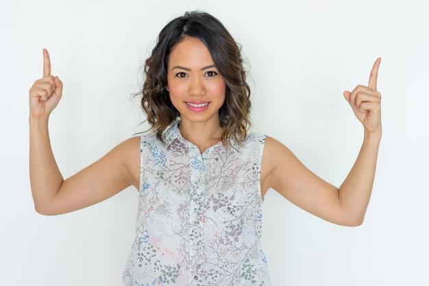 Souriante jeune femme pointant vers le haut avec les deux index Photo gratuit