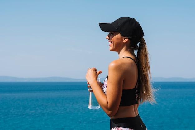 Souriante jeune femme portant casquette debout devant la mer, tenant une bouteille d'eau à la main Photo gratuit