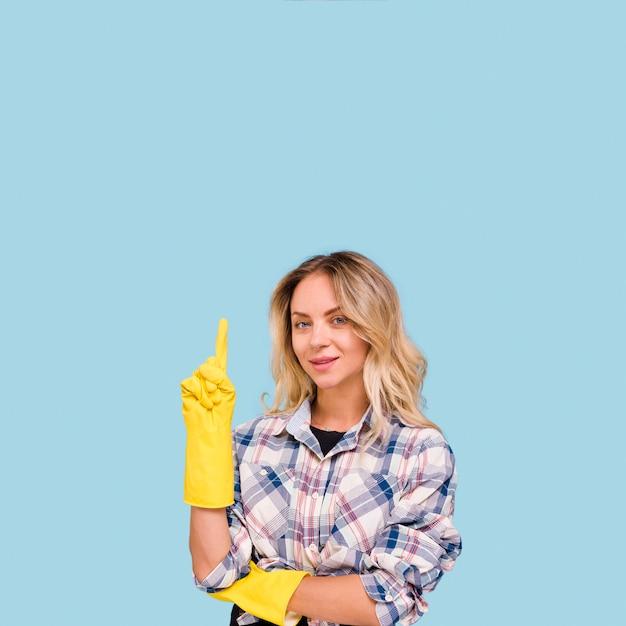 Souriante jeune femme portant un gant jaune pointant vers le haut, debout contre le mur bleu Photo gratuit