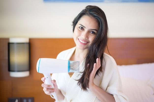Souriante Jeune Femme Portant Un Peignoir Blanc Séchant Ses Cheveux Avec Un Sèche-cheveux Après Une Douche Dans La Chambre Photo Premium
