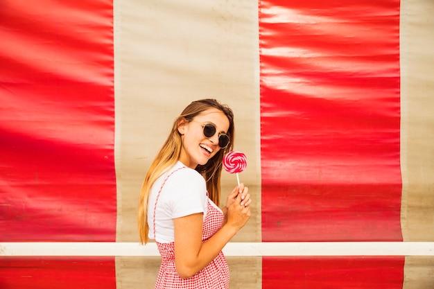 Souriante jeune femme posant avec sucette Photo gratuit
