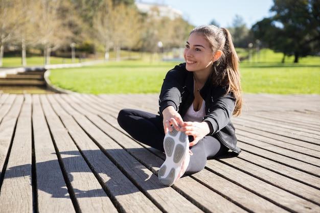 Souriante jeune femme qui s'étend de la jambe à l'extérieur Photo gratuit