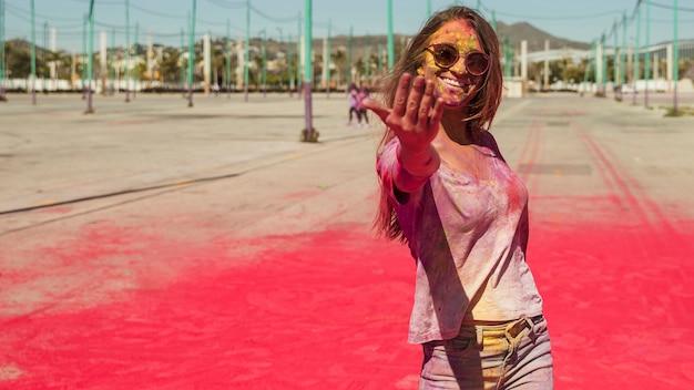Souriante jeune femme recouverte de couleur holi appelant devant la caméra Photo gratuit