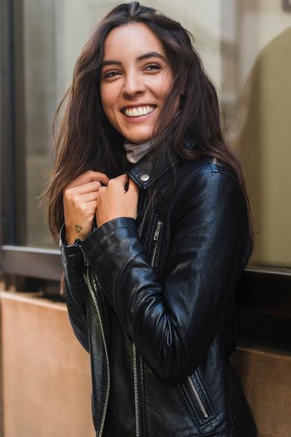 Souriante jeune femme regardant la caméra portant la veste noire Photo gratuit