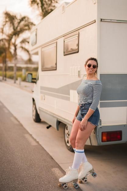 Souriante Jeune Femme Se Penchant Sur La Caravane Photo gratuit